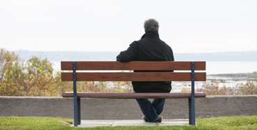 Seen from behind, a man sits alone on a bench looking at the sea