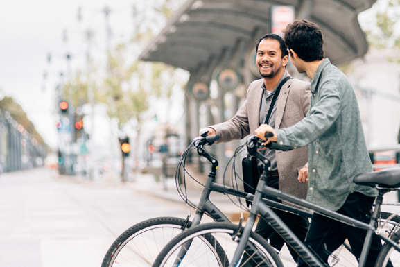 A young Asian man smiles at his male partner. Both are walking their bikes in downtown San Francisco.
