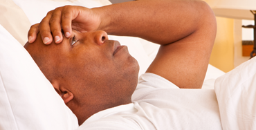 A black man in bed during the daytime. He has a flat expression with his hand to his head