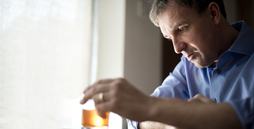 A middle-aged white man in a dress shirt, wearing a wedding ring, holds a glass of whiskey. He looks at it with a defeated expression.