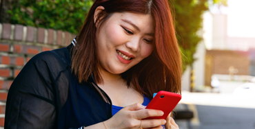 A Korean woman smiles as she reads a message on her phone
