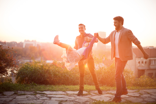 A young gay couple, both white men, swing their daughter in the air